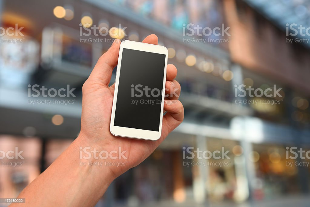 Hand holding smartphone, customizable blank display, defocused shopping mall background stock photo