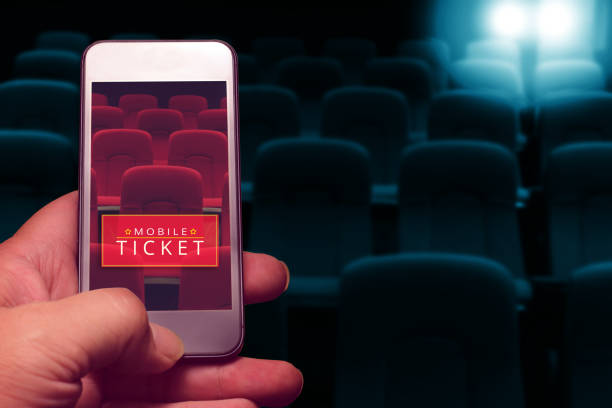 hand holding smartphone for reserved movie ticket. online ticket buying. - hand holding phone zdjęcia i obrazy z banku zdjęć