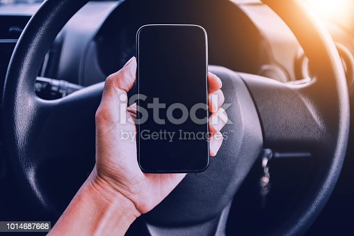 istock Hand holding smartphone in car parked on street.And using smartphone to shopping online by internet 1014687668