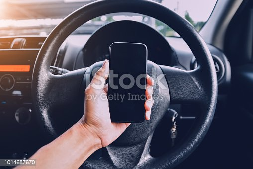 istock Hand holding smartphone in car parked on street.And using smartphone to shopping online by internet 1014687670
