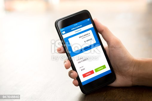 istock Hand holding smartphone showing online electronic internet banking application on screen 947648840