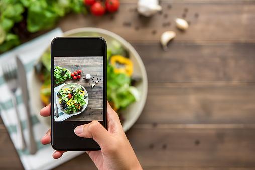 Hand holding smartphone taking photo of beautiful food, mix fresh green salad