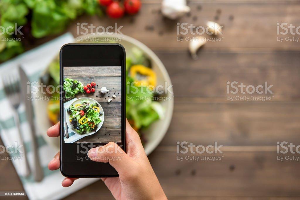 Hand halten Smartphone Foto schön essen, frischen grünen Salat mischen – Foto
