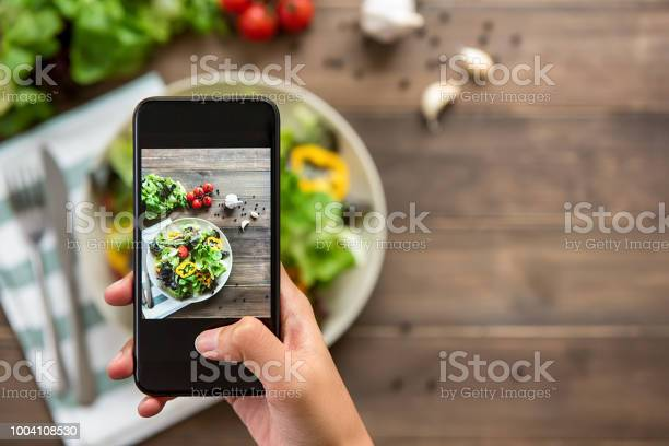 Food blogger using smartphone taking photo of beautiful mix fresh green salad on wood table to share on social media