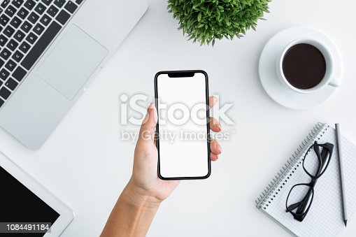 1084491176 istock photo Hand holding smartphone with big blank screen 1084491184