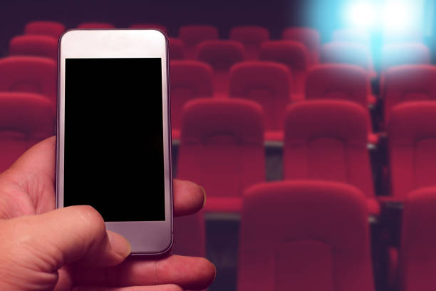 hand holding smartphone with black screen and row of red seat background. online ticket buying concept. - hand holding phone zdjęcia i obrazy z banku zdjęć