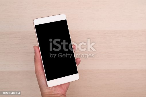 1084491176 istock photo hand holding smartphone with blank screen isolated on wooden background 1059046964
