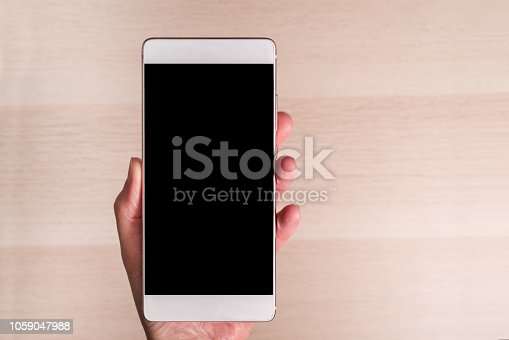 istock hand holding smartphone with blank screen isolated on wooden background 1059047988