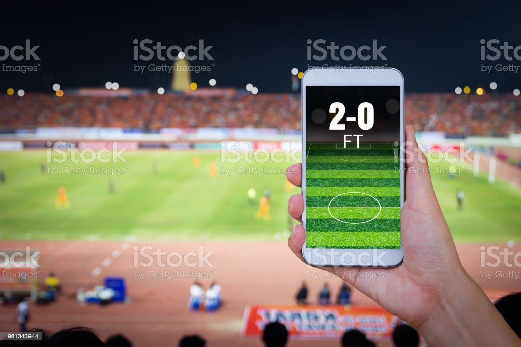 Hand holding smartphone with blur football field background. stock photo