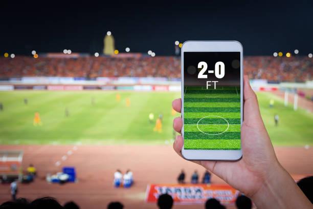 Hand mit Smartphone mit Unschärfe Fußball Feld Hintergrund. – Foto