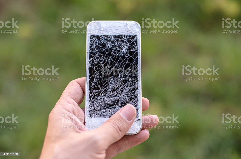 Hand holding smartphone with broken screen stock photo