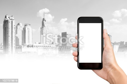 1023041738istockphoto Hand holding smartphone with  city buildings in background 1027578616