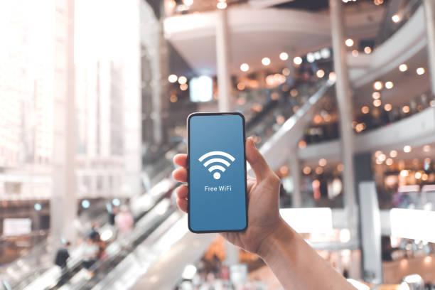 Hand hält Smartphone mit kostenlosem WLAN-Symbol auf verschwommenem Einkaufszentrum Hintergrund. – Foto