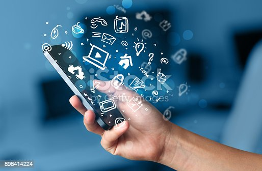 istock Hand holding smartphone with media icons and symbol 898414224