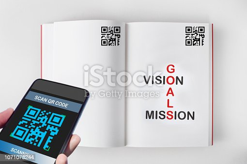 istock Hand holding smartphone with scanning QR code on book screen with words of goals, vision and mission on book 1071078244