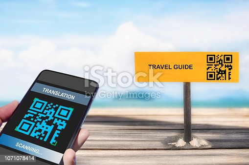 istock Hand holding smartphone with scanning QR code translation screen with travel guid sign on tropical beach background 1071078414