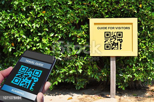 istock Hand holding smartphone with scanning QR code travel guide screen with guide for visitors sign 1071078494