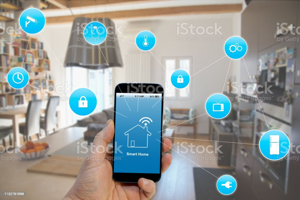 Hand holding smartphone with smart home application on screen Smart Home concept, Appliance Stock Photo