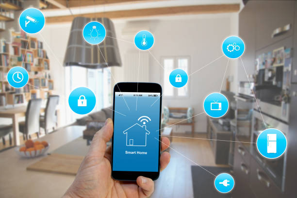 hand holding smartphone with smart home application on screen - home automation stock pictures, royalty-free photos & images