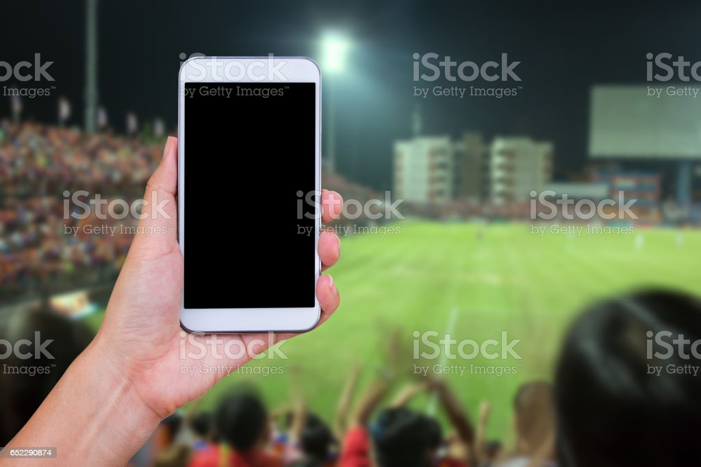 Hand holding smartphone with soccer screen in football stadium background. stock photo