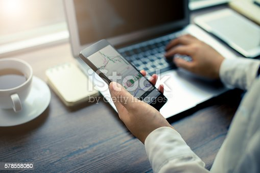 istock Hand holding smartphone with stock graph 578558080
