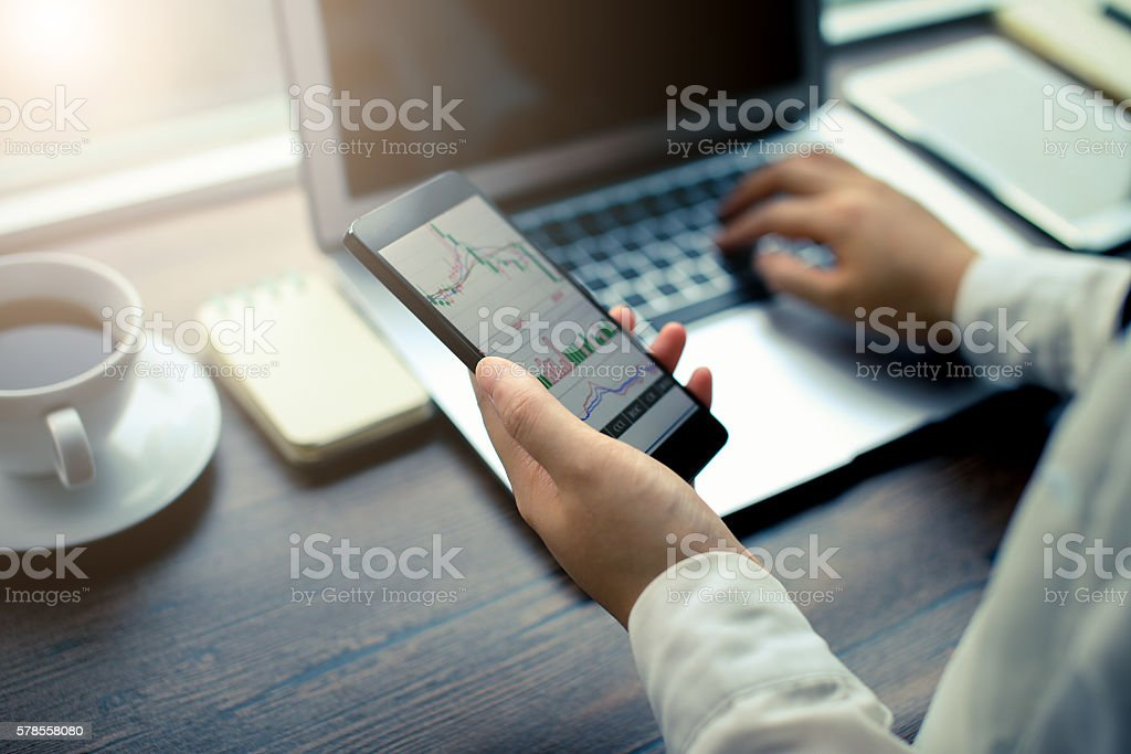 Hand holding smartphone with stock graph stock photo