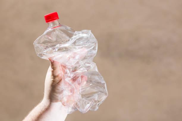 Handhalten zertrümmertleere Plastikflasche isoliert auf einem verschwommenen Hintergrund. Recycling- und Freiwilligenkonzept. Umweltverschmutzung und weltweites ökologisches Problem – Foto
