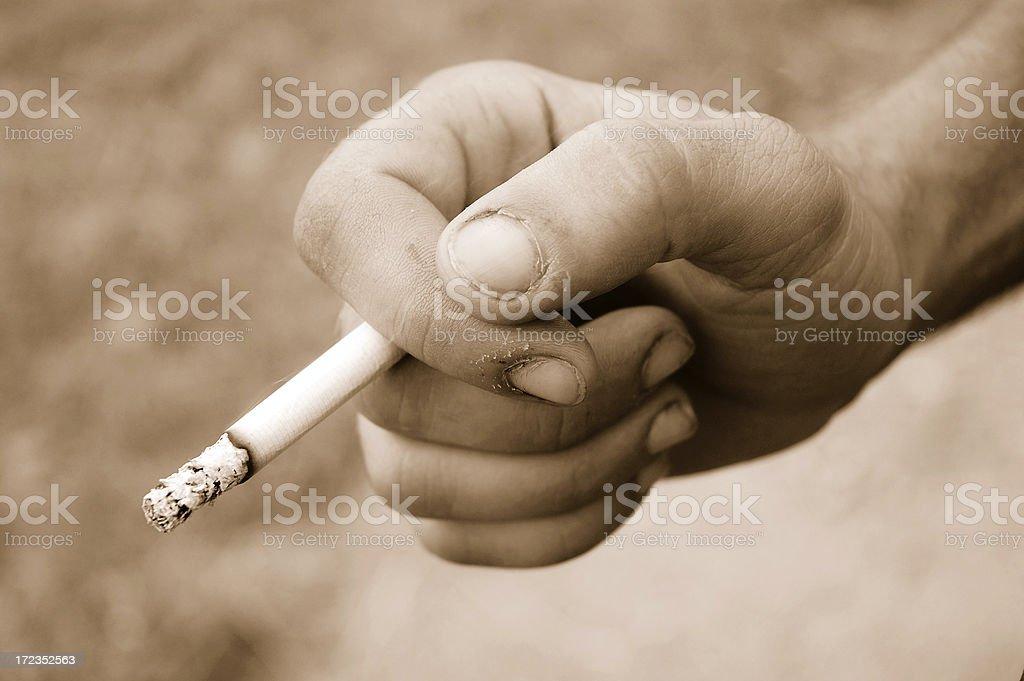 Hand holding smoking Cigarette royalty-free stock photo