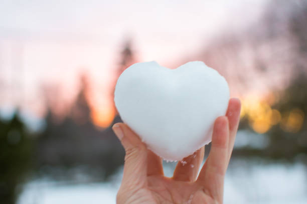 Hand holding snow heart with beautiful pink sunset sky in winter stock photo