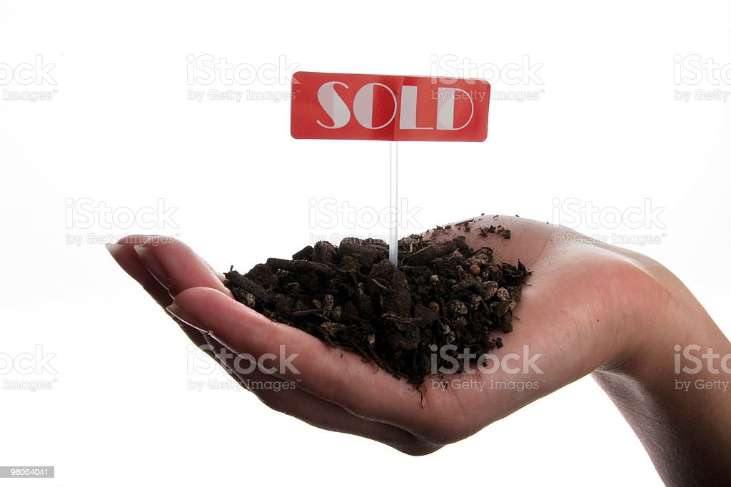 Hand holding sold sign and soil royalty-free stock photo
