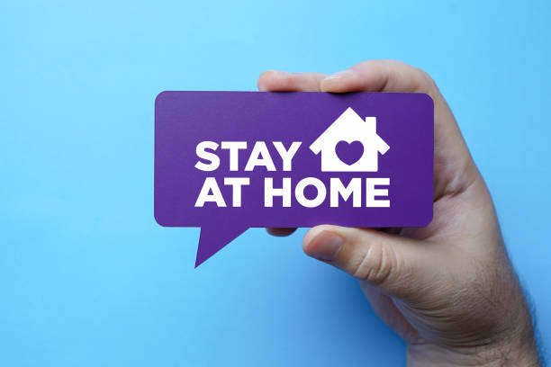 Hand holding speech bubble with stay at home. stock photo