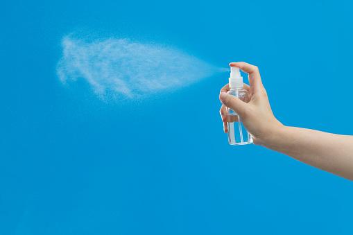 Hand holding spray bottle on blue background.