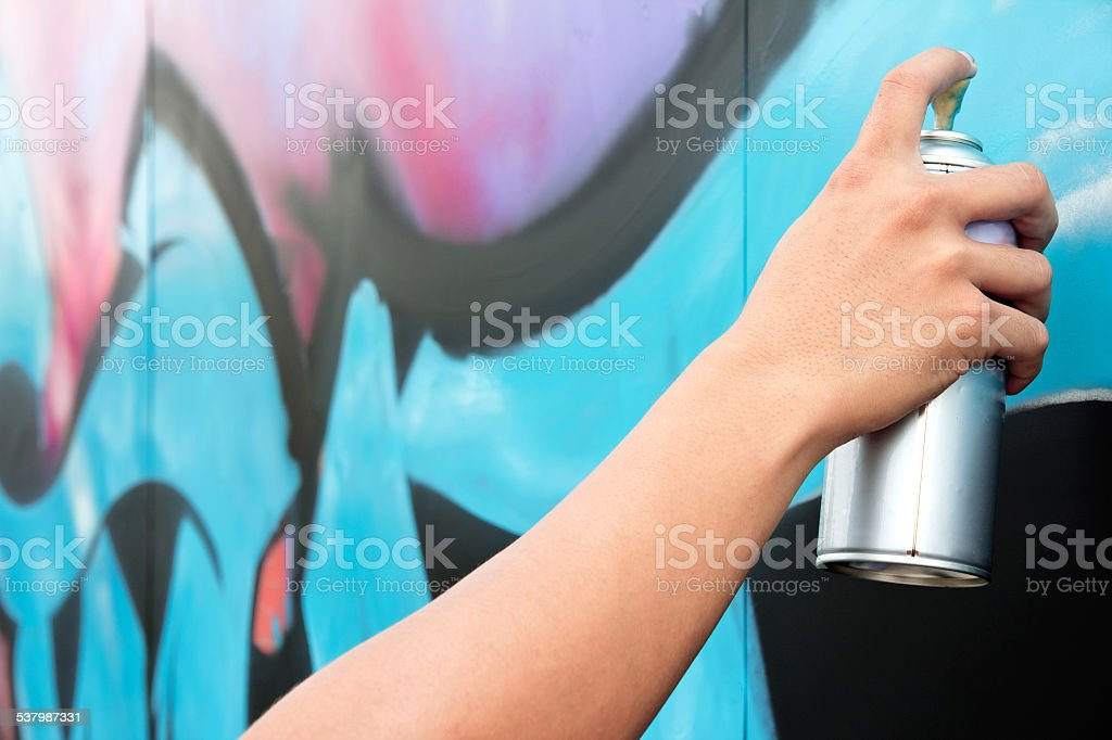 Hand holding spray paint on the wall graffiti stock photo