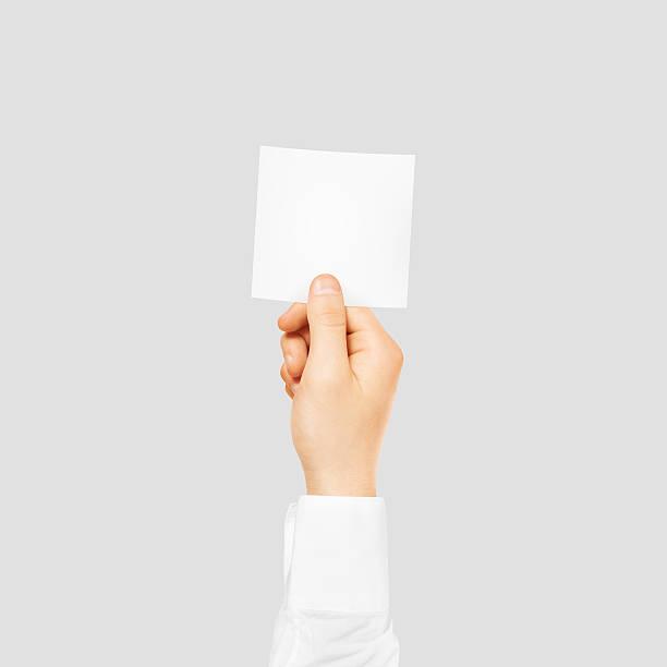hand holding square blank white sticker mock up isolated on - flyer inspiration stock-fotos und bilder