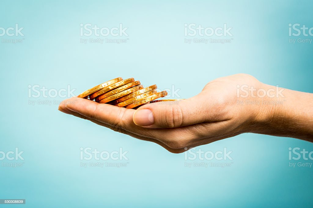 Hand holding stack golden coins. Taxpayer/Crowdfunding concept stock photo