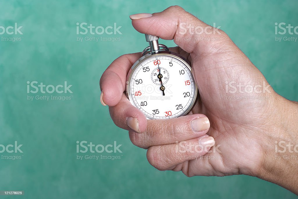 Hand holding stopwatch against green background stock photo