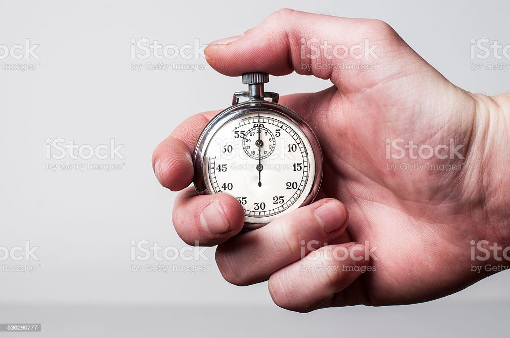 Hand holding stopwatch stock photo