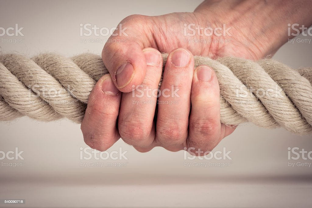 Hand holding strong rope stock photo