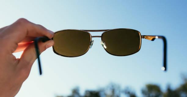 Hand holding sunglasses outdoors blue sky sunbeam and lens flares picture id1192258623?b=1&k=6&m=1192258623&s=612x612&w=0&h=y6q0cdz9zgyrnlkg6mnjholqojqvktsdepovseb0r8a=