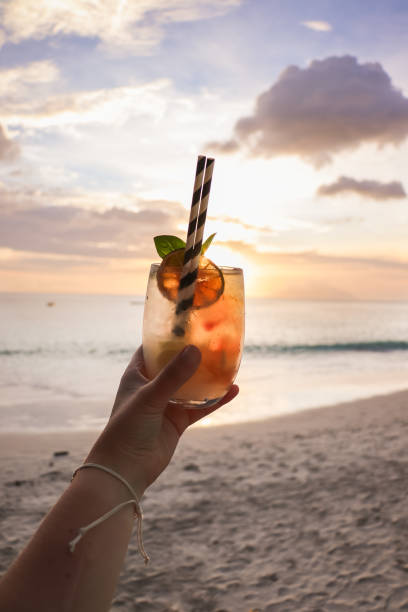 hand holding sunset cocktail