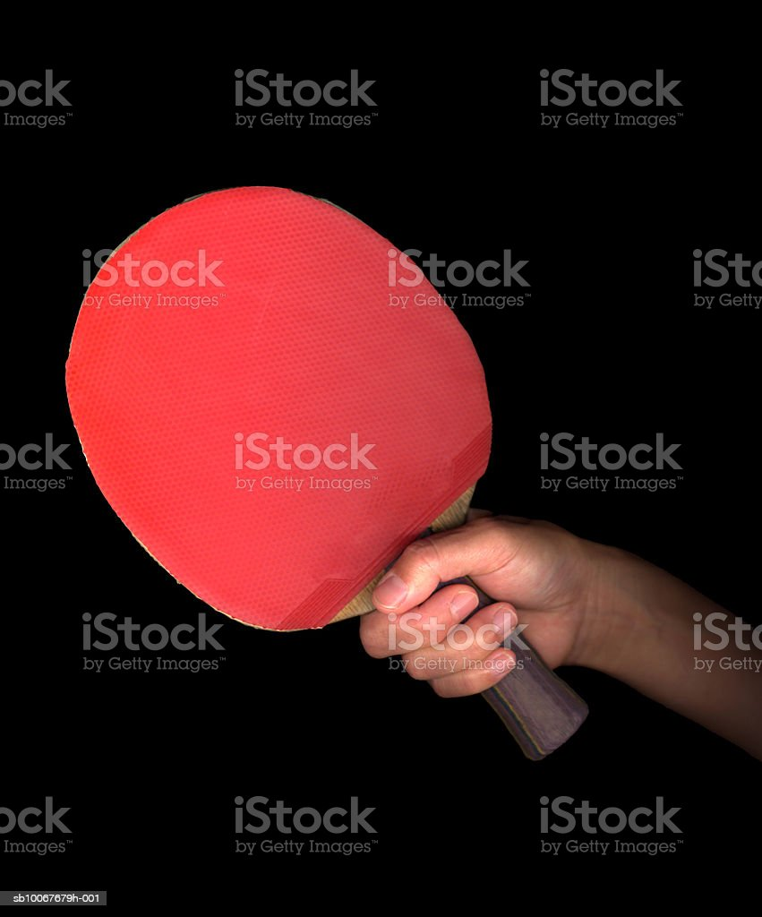 Hand holding table tennis paddle, on black background royalty-free stock photo