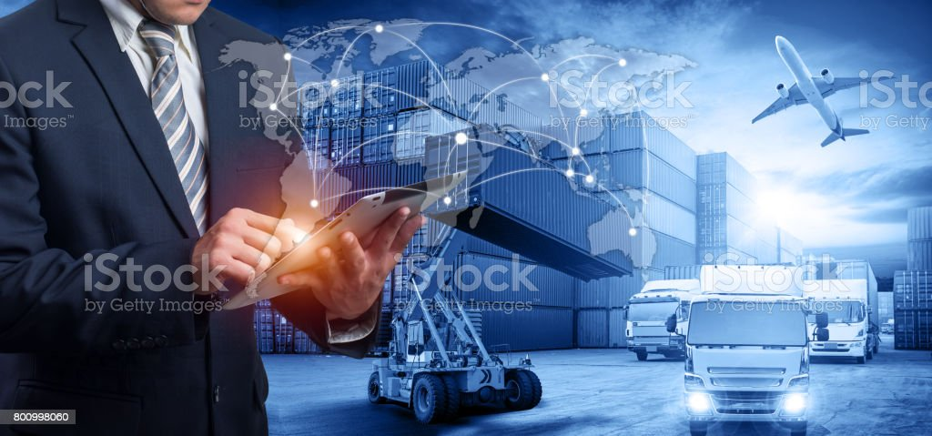 Hand holding tablet is pressing button on touch screen interface in front Logistics Industrial Container Cargo freight ship stock photo