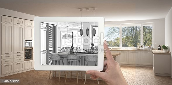 952643774 istock photo Hand holding tablet showing kitchen sketch or drawing. Real finished modern kitchen with island and stools in the background, architecture interior design presentation 943758822