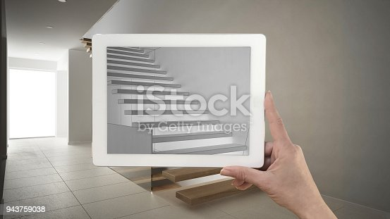 952643774 istock photo Hand holding tablet showing modern stairs sketch or drawing. Real wooden stairs in the background, architecture interior design presentation 943759038