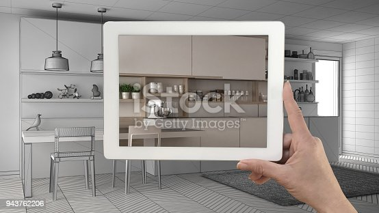 894638730 istock photo Hand holding tablet showing real finished minimalist white and wooden kitchen. Modern kitchen sketch or drawing in the background, architecture interior design presentation 943762206