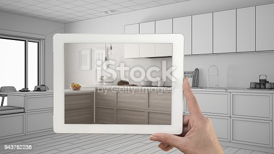 894638730 istock photo Hand holding tablet showing real finished minimalist white and wooden kitchen. Modern kitchen sketch or drawing in the background, architecture interior design presentation 943762238