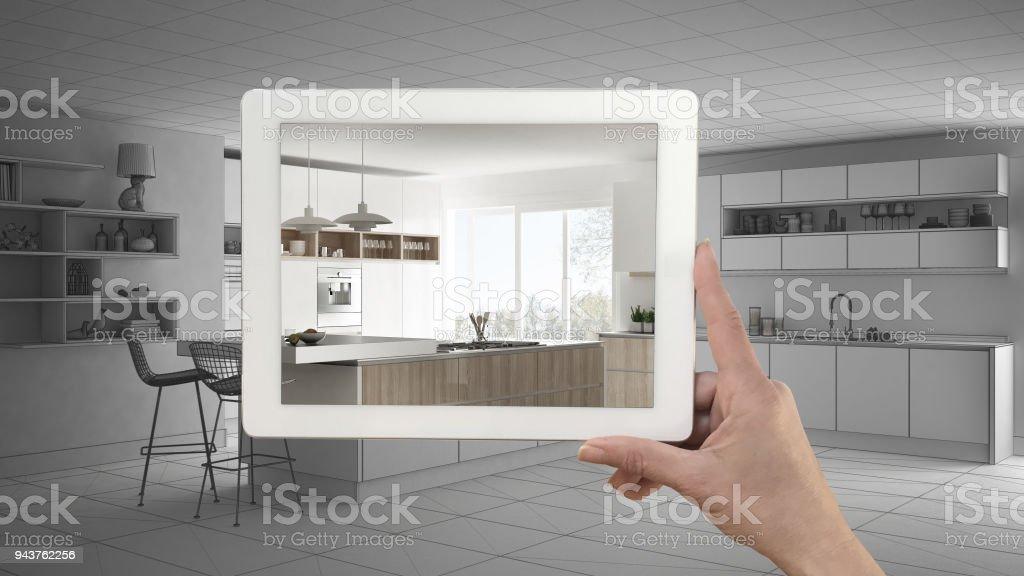 Hand met tablet tonen echte eindigde moderne keuken met eiland en