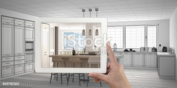 894638730 istock photo Hand holding tablet showing real finished modern kitchen with island and stools. Kitchen sketch or drawing in the background, architecture interior design presentation 943762302