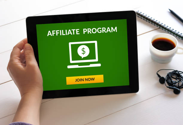 Hand holding tablet with affiliate program concept on screen Hand holding digital tablet computer with affiliate program concept on screen. All screen content is designed by me affiliate stock pictures, royalty-free photos & images