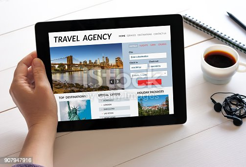Hand holding digital tablet computer with travel agency concept on screen. All screen content is designed by me